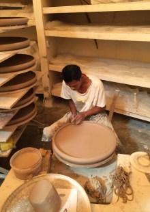 Man making ceramic bowl on pottery wheel
