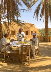 Three men at table under palm trees