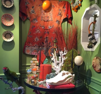 Interior with green wall, woven baskets, red silk kimono, table with mounted coral, alligator skull, mounted ostrich egg, and glass jellyfish