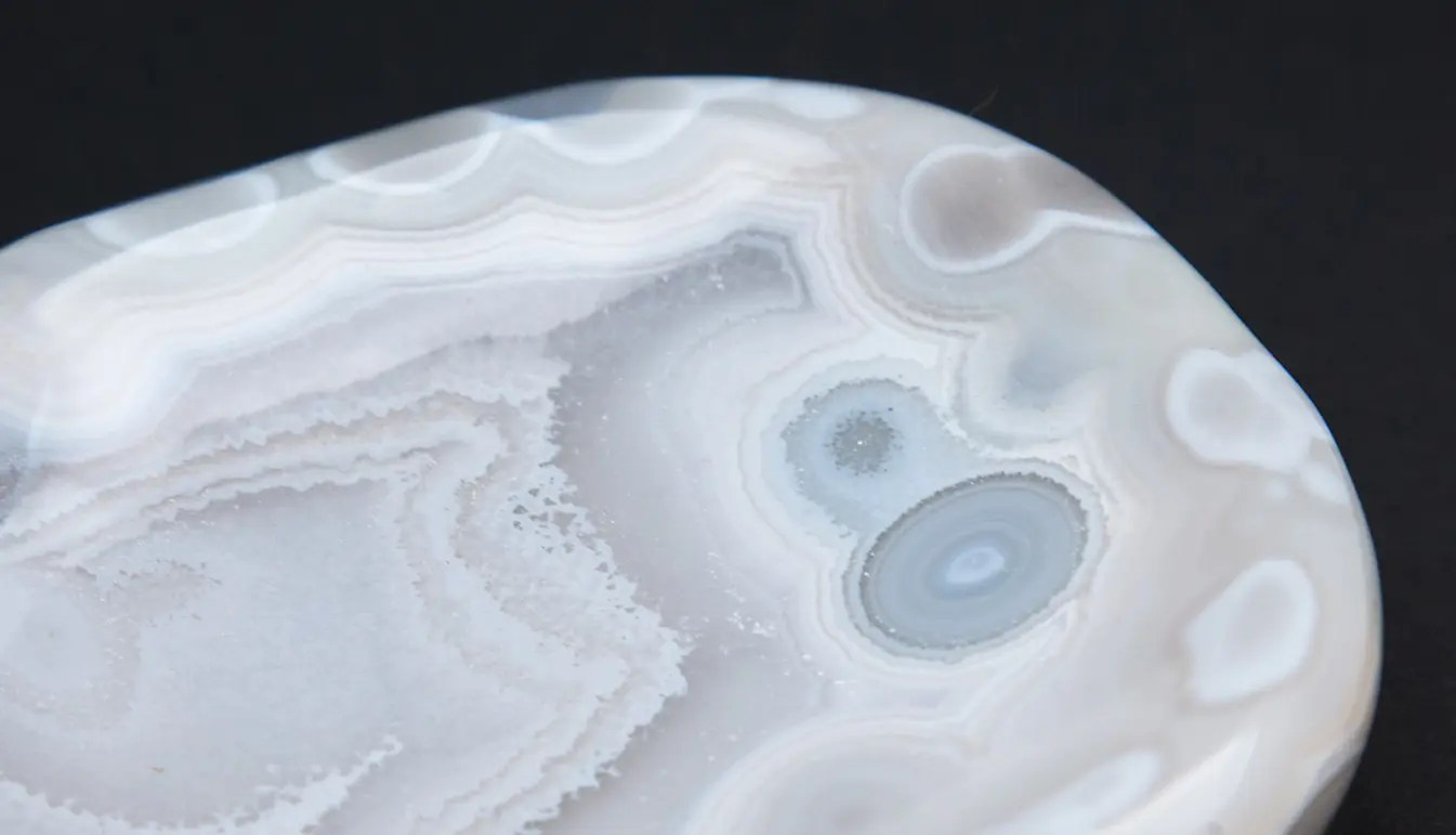 closeup of edge of Agate vide poche with bands of light blue, white, brown, with amorphous shape. Resting on black background