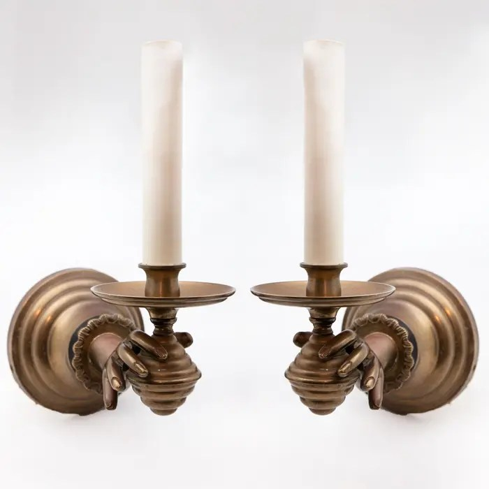 PAir of hands holding candles wall sconces