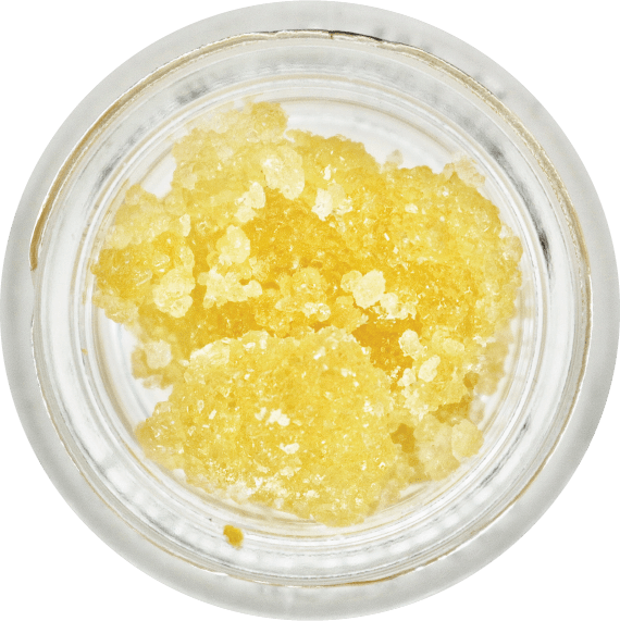 Small THC-A diamonds that are bright yellow from terpenes they've soaked up, sitting in a jar.
