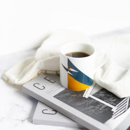 Kingshier mug with coffee on magazines