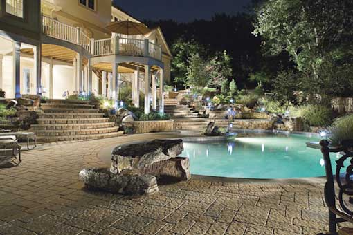 techo-bloc-pool-at-night-with-jumping-diving-board-made-out-of-stone-nice-second-story-patio