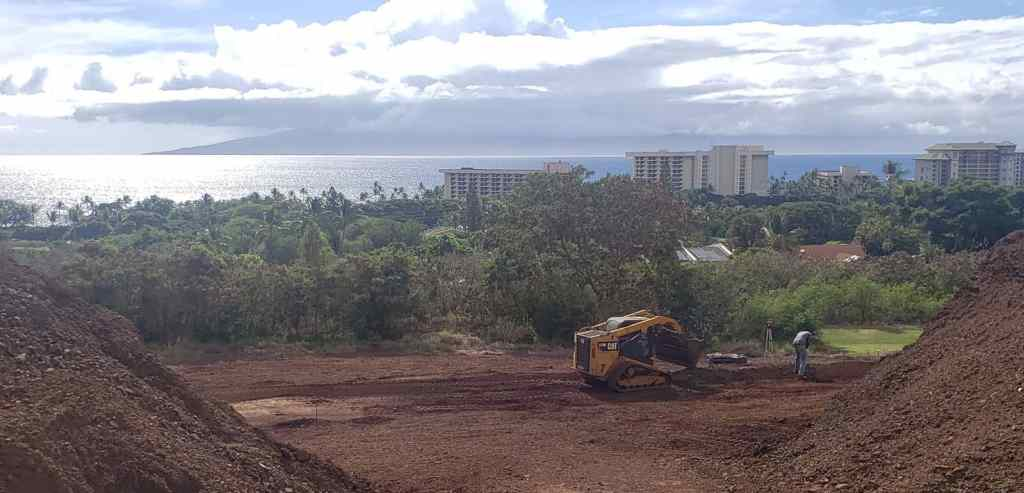 Maui excavation contractor and worker with hills of soil on a new home project.