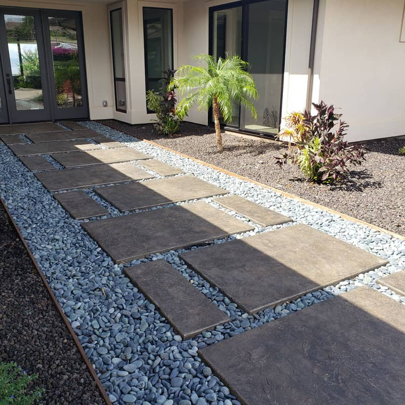 Concrete walkway surrounded by decorative stones