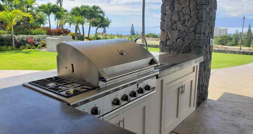 Outdoor kitchen grill and concrete counters with ocean view.