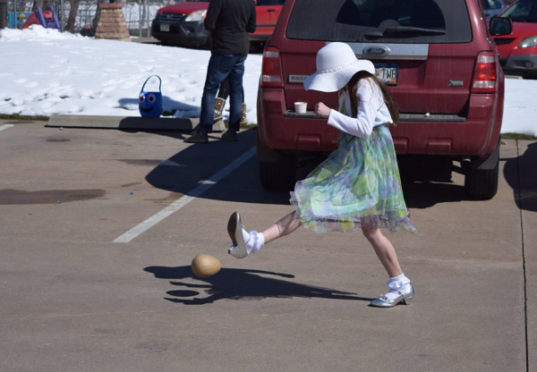 Photo taken on Easter Sunday with young girl kicking a ball in the parking lot.