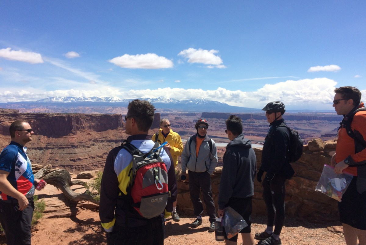 Photo of men on canyon rim lookout during the annual men's Moab retreat.