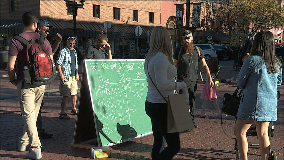 Photo of Pastor Mark engaging on the Pearl Street Mall in Boulder, with chalk board.