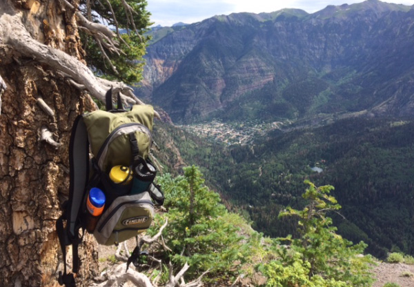 Photo of backpack hanging on a tree branch high above a valley floor.