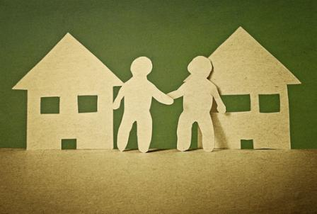 Image of a paper cutout of two neighbors shaking hands in front of their houses.