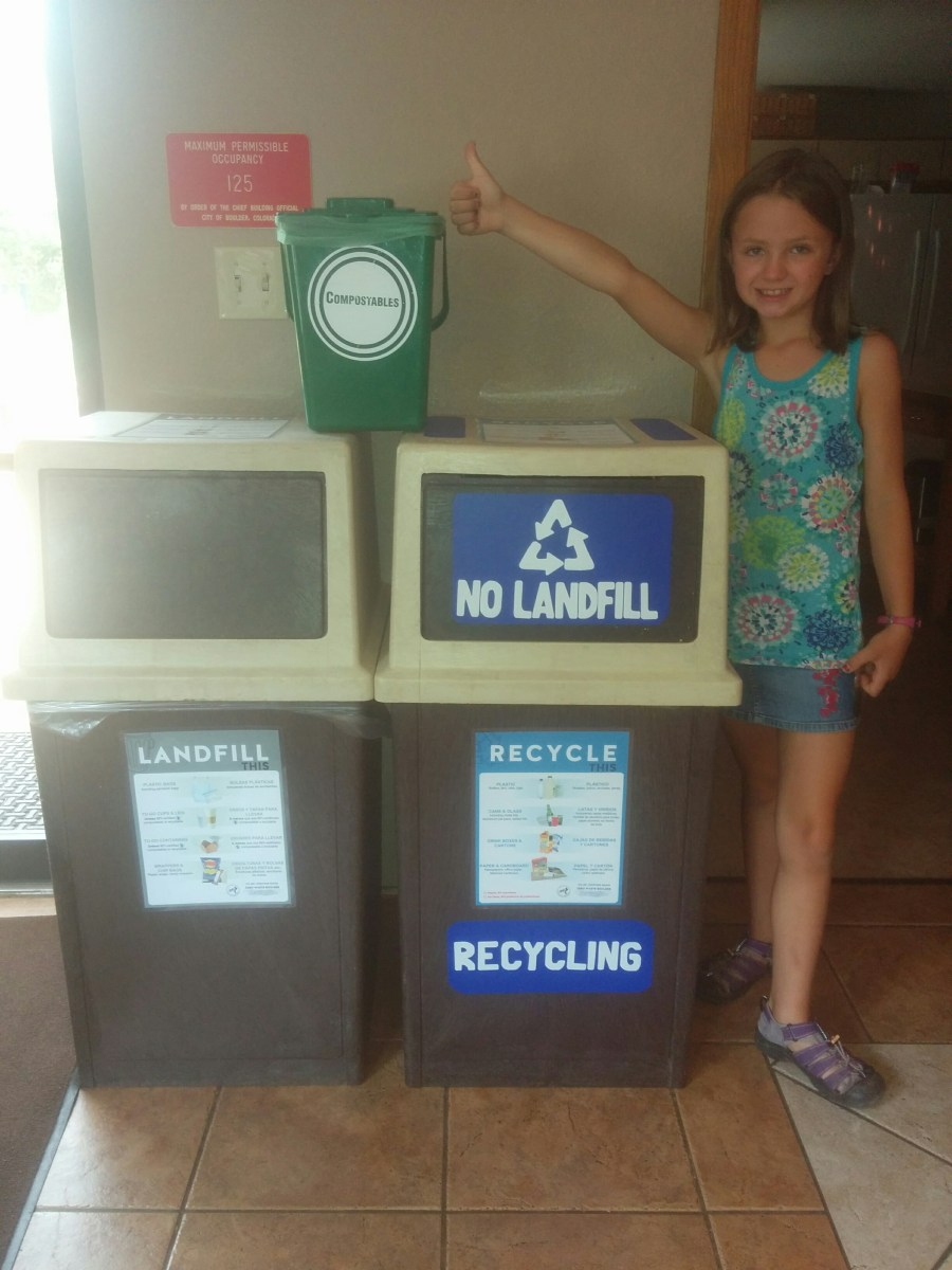 Photo of Anna standing by recycling cans and compost bin and giving the thumbs up for zero waste initiative at Crestview!