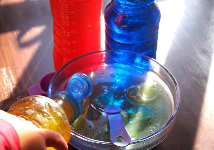 Juegos de transvases de liquido de colores con reflejos de la luz natural