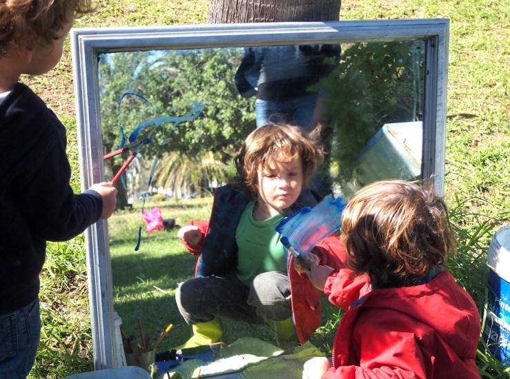 Niño pintando en el espejo con su imagen reflejada