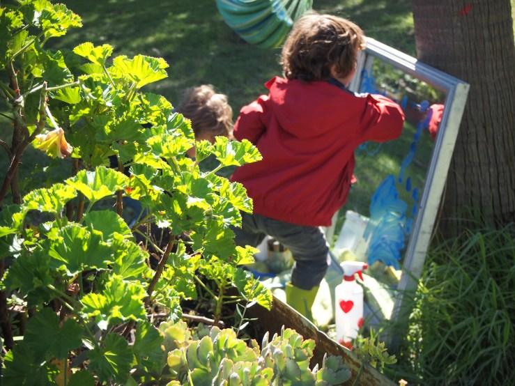 Niños pintando alegremente en el espejo en el exterior