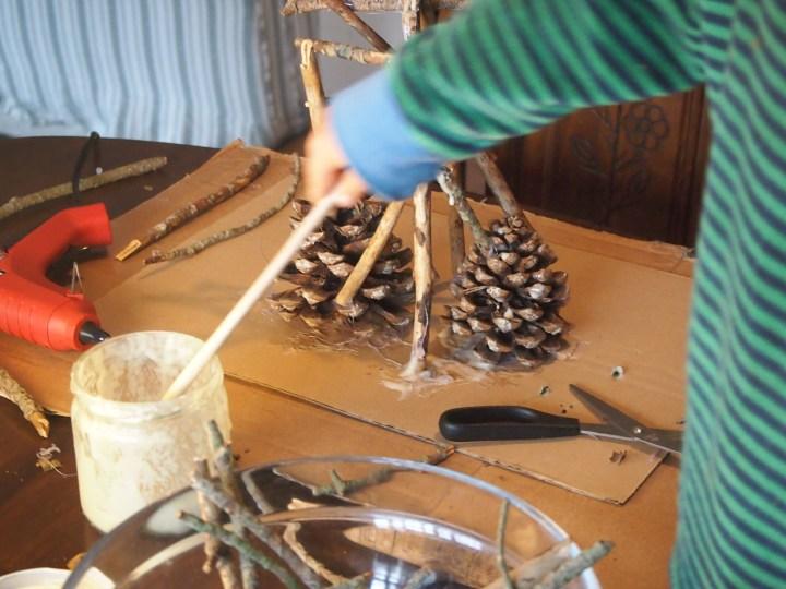 colocando y pegando los palos encima de las piñas