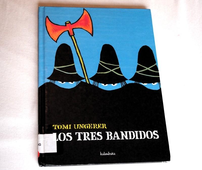 Portada de: Los tres bandidos. Fondo azul y siluetas de bandidos con corro y hacha