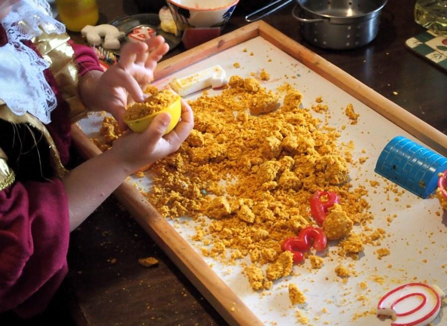 Manos de niños jugando con la masa sensorial de harina de piel de mandarina