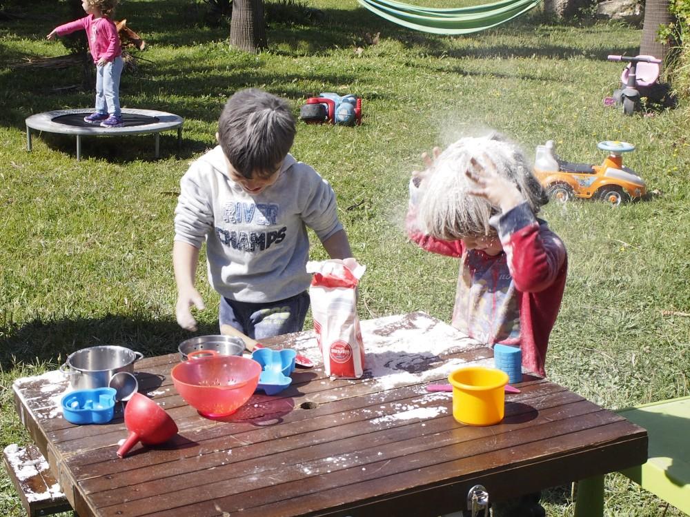 Nisños echandose harina por encima de la cabeza en el grupo de juego