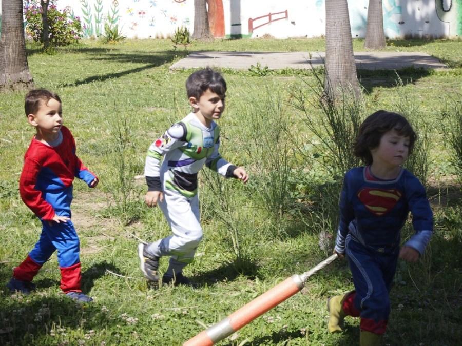 Niños disfrazados corriendo por la pradera de cesped en el parque