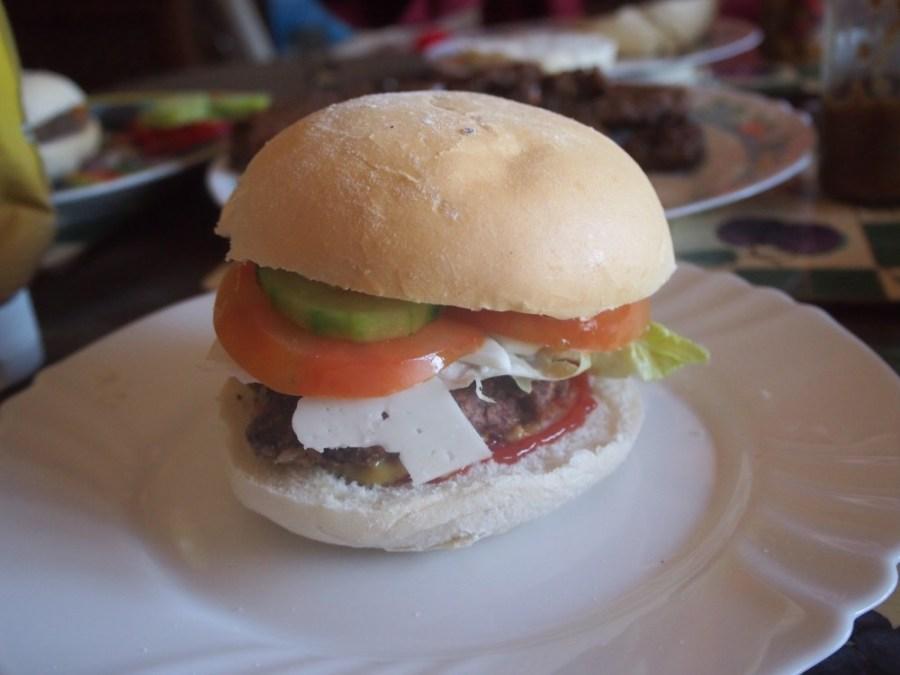 Hamburguesa veetariana de judias servida con pan y ensalada, queso y salsas