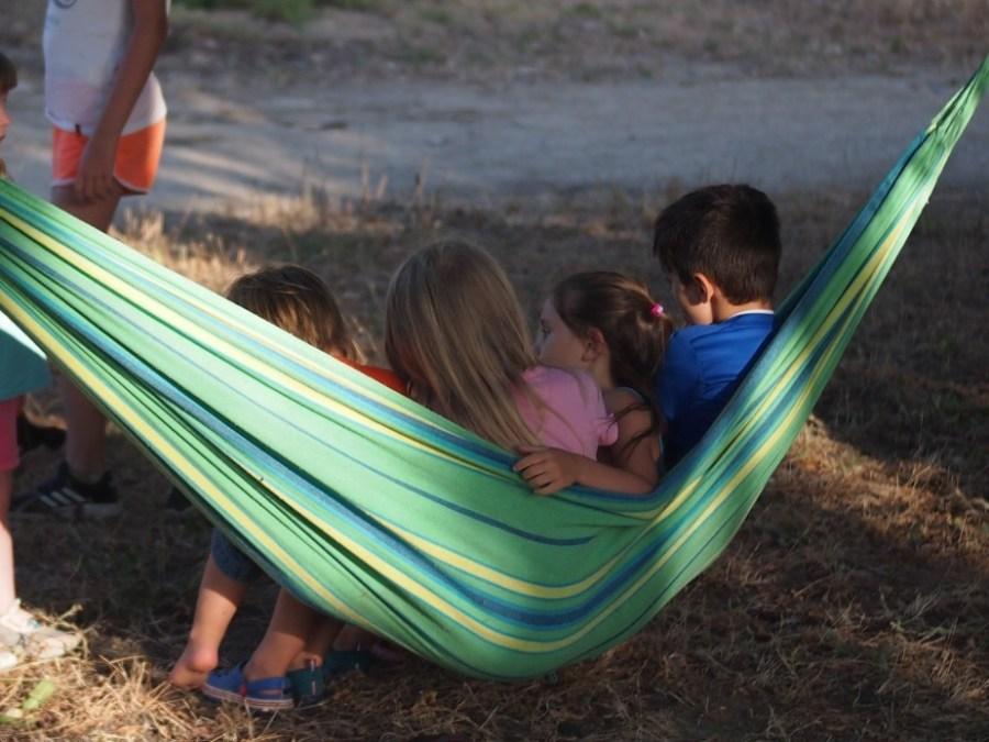 Niños sentados en una hamaca balanceandose y hablando