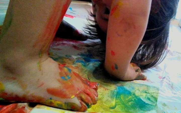 Niño pintando con las manos. Portada del grupo jugar en casa