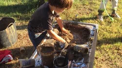 Niño con manos en el barro en el grupo de juego del parque
