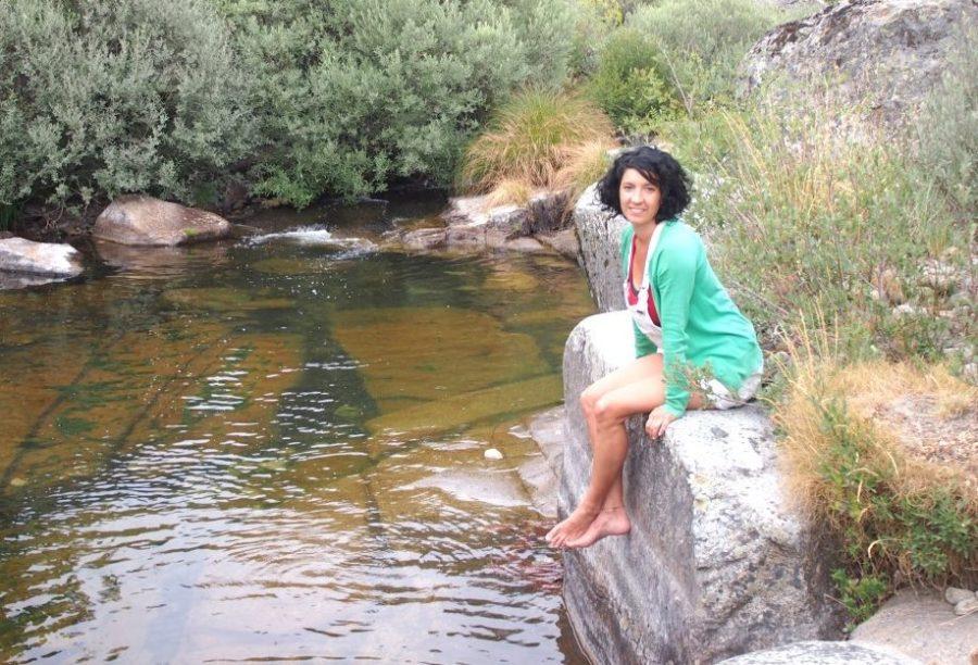 Llanos en la orilla de un rio sentada en uan piedra