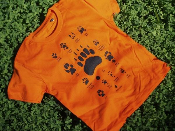 Camiseta de huellas y hojas color naranaja