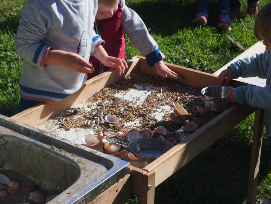 Juegos sensoriales con pipas, alpiste, conchas arena y cacharritos en el grupo de juego al aire libre