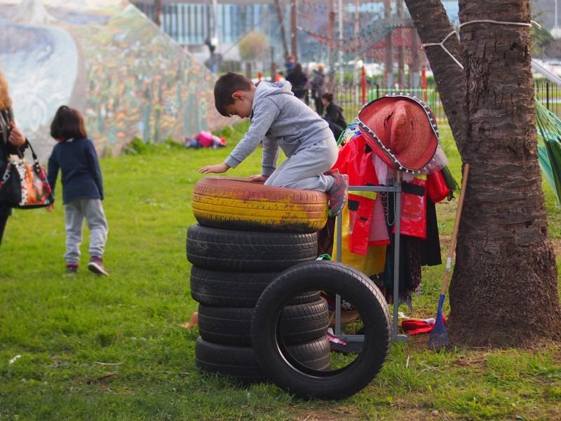 Niño escalando un monton de neumaticos reciclados