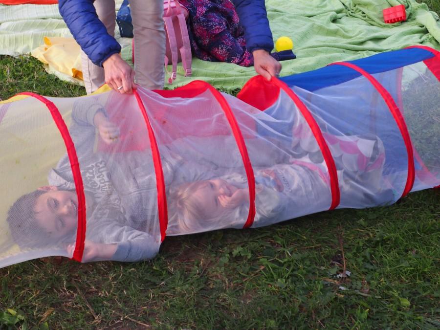 Niños jugando en un tubo transparente con una madre. Una de las normas del grupo de juego es jugar con tus hij@s