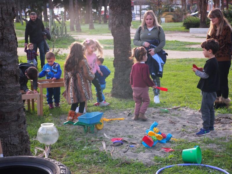 Niños y niñas jugando en el arenero. Familias acompañando que es una de las normas del grupo de juego
