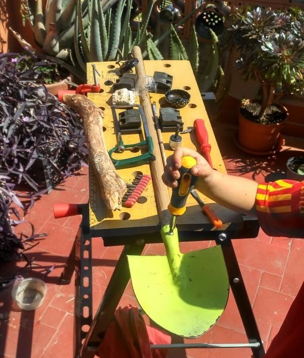 Restauración con niños, arreglando su pala de madera y metal en la terraza en el banco de trabajo