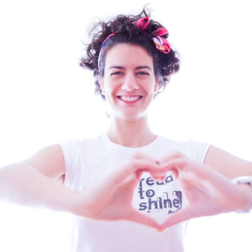 Foto de Nora de Nora oils con fondo blanco y haciendo un corazón con la mano.