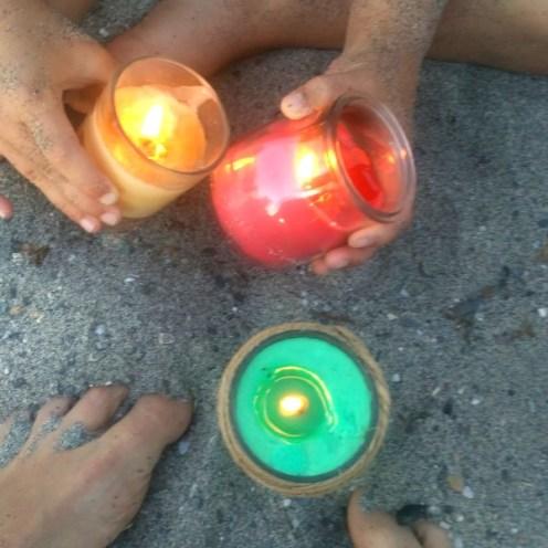 Manos de niño manejando unas velas de colores en un ritual con niños en la playa