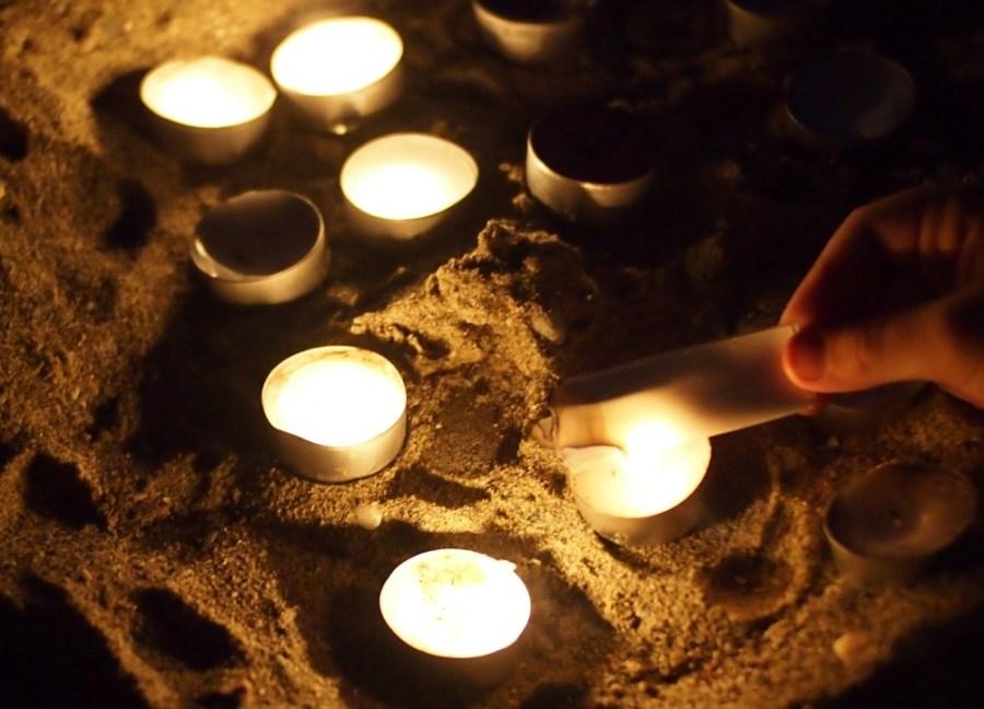 Mano deniño quemando un papel en un ral con velas
