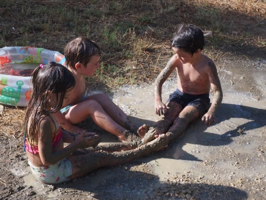 Niños en bañador tomando un baño de barro en el suelo
