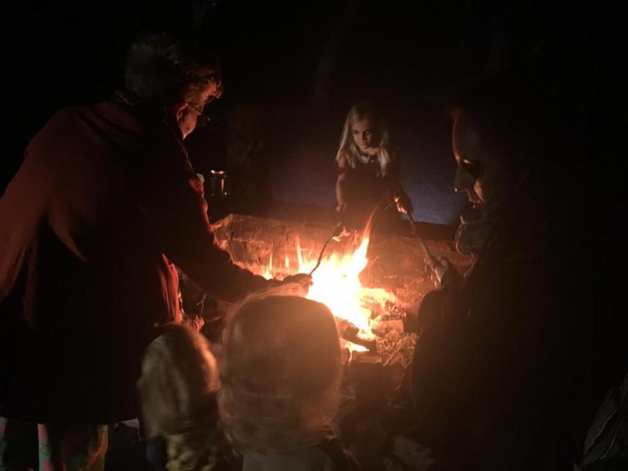 Asando masa de pan y castañas en una fogata para celebra halloween