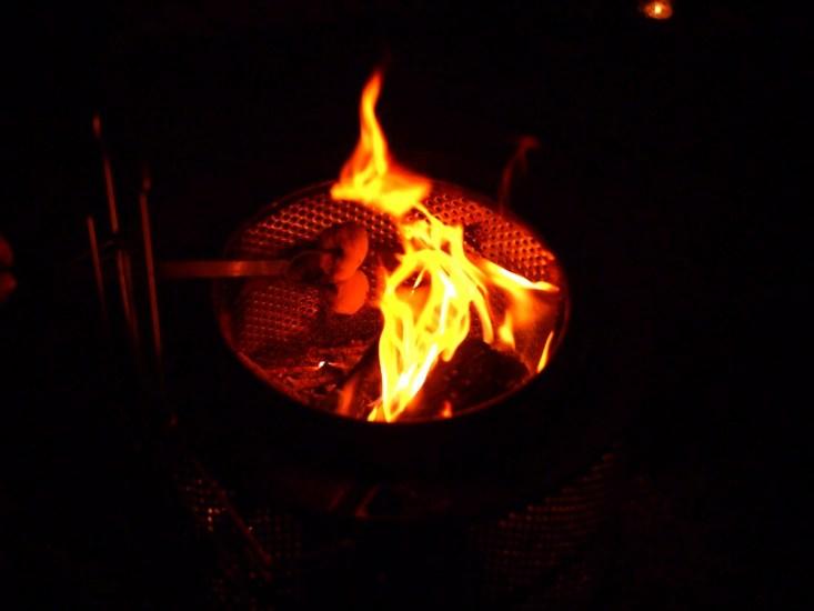 Palo con masa de pizza al fuego de la fogata de Halloween o Samain
