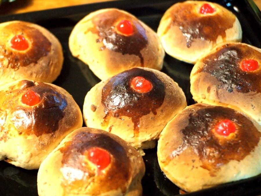 Panecillos dulces con forma de teta y cereza confitada como pezón al salir del horno
