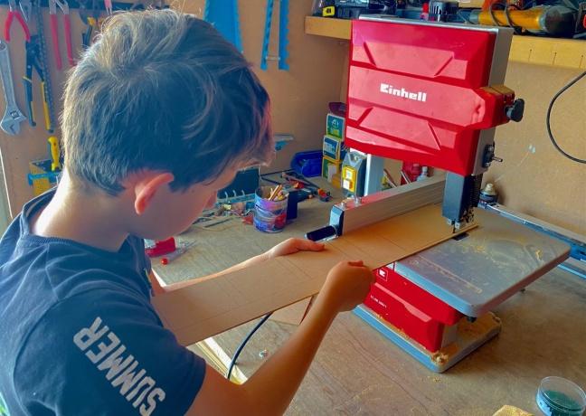Niño cortando una madera en un taller con maquinaria