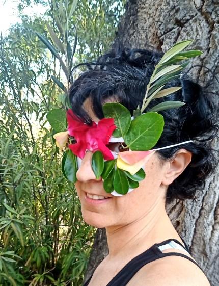 Mujer con mascara decorada con hojas y flores para la luna de las flores