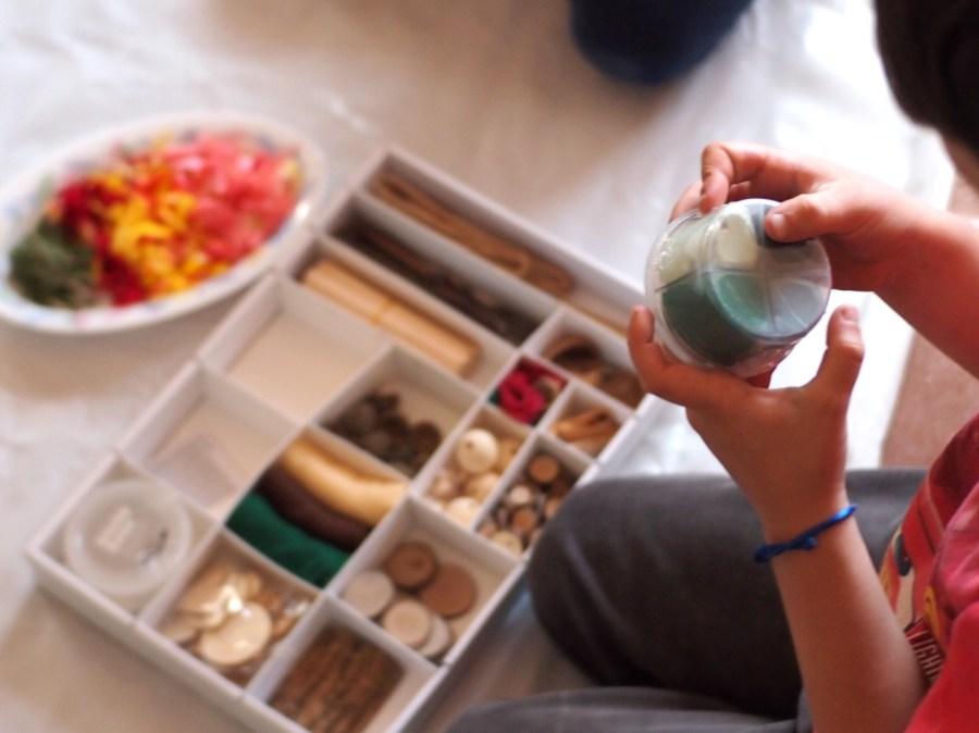 Manos de niño abriendo el bote de pasta de modelar y la caja de piezas sueltas naturales detrás