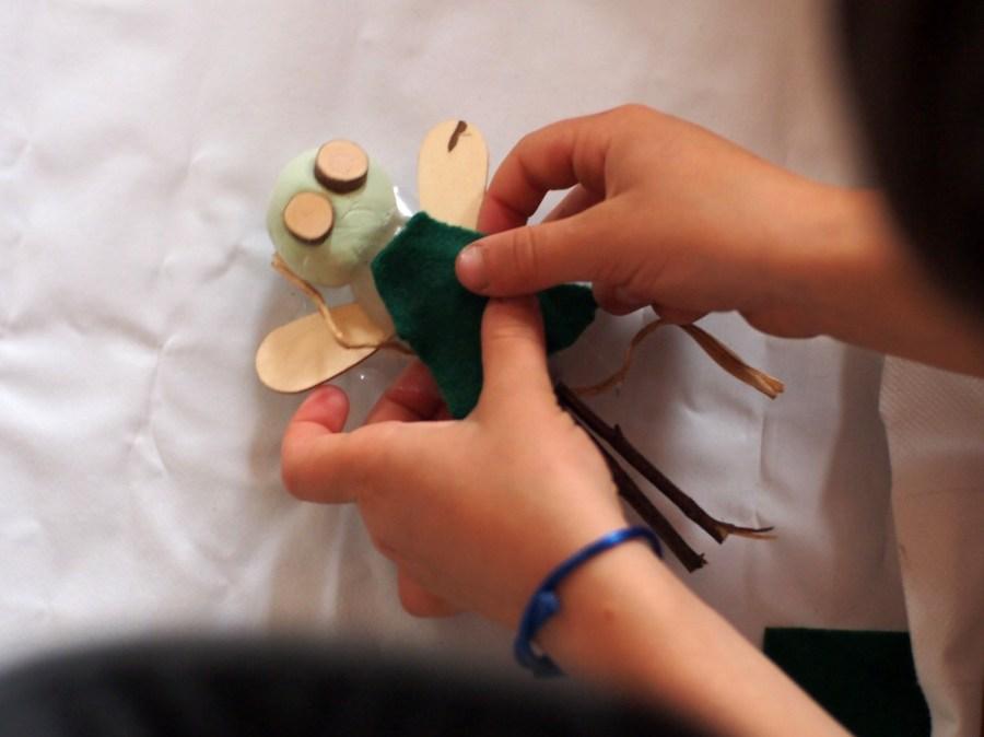 Manos de niño poniendo tela encima de una hada hecha de pasta de modelar y elemetos naturales