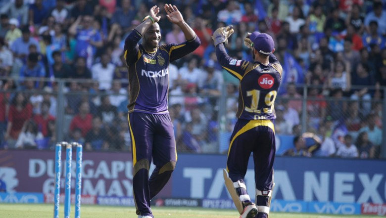 Kolkata Knight Riders' Andre Russell, left, celebrates the dismissal of Mumbai Indian's Evin Lewis with his team captain Dinesh Karthik