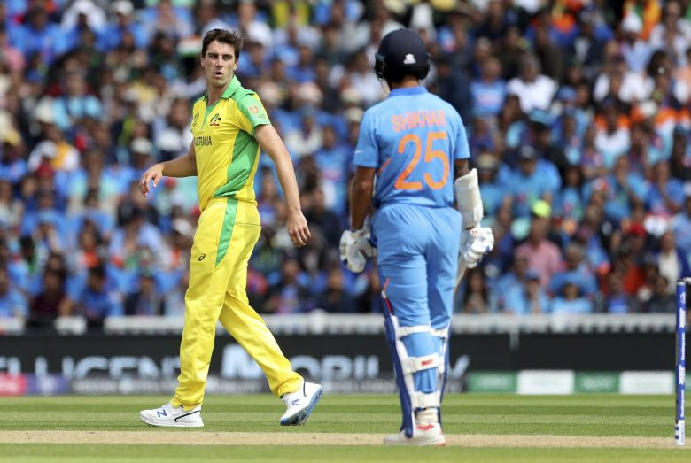 Australia's Pat Cummins, left, reacts after bowling a delivery to India's Shikhar Dhawan
