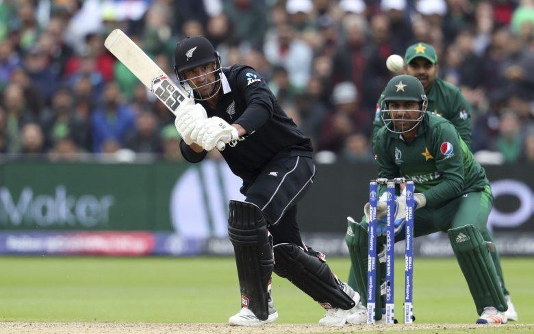New Zealand's batsman Colin de Grandhomme, left, watches his shot as Pakistan's captain Sarfaraz Ahmed watches on